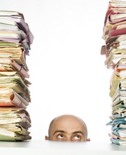 man looking up at stacks of files