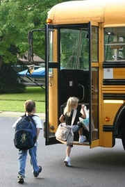 young students getting on bus
